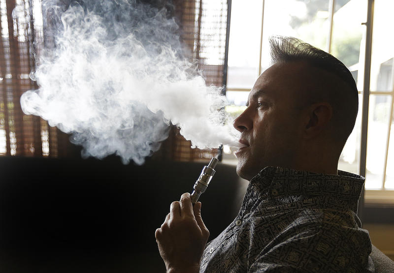 Geoff Braithwaite, owner of Tasty Vapor, exhales vapor after using an electronic cigarette Wednesday, Jan. 28, 2015 in Oakland, Calif.
