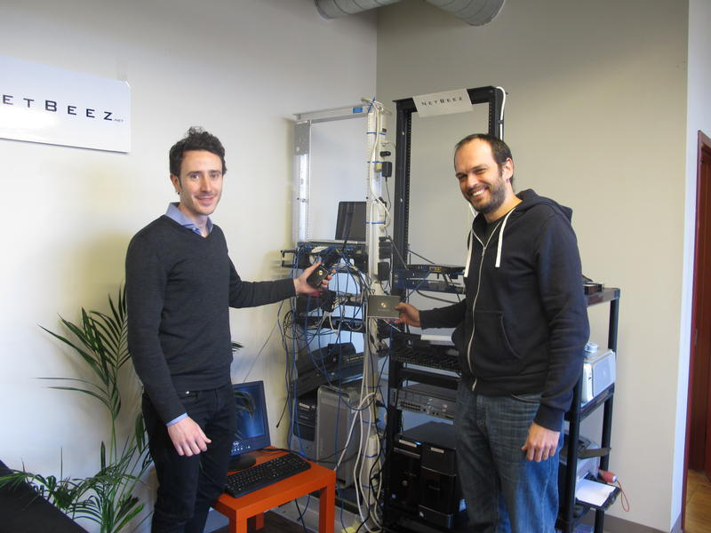 NetBeez Co-founders Stefano Gridelli (L) and Panickos Neophytous hold the small devices that are installed at remote offices to help IT professionals monitor connectivity.