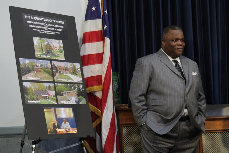 Howard Slaughter, executive director of Habitat for Humanity of Greater Pittsburgh, stands next to photos of the five homes his organization purchased from Allegheny County.