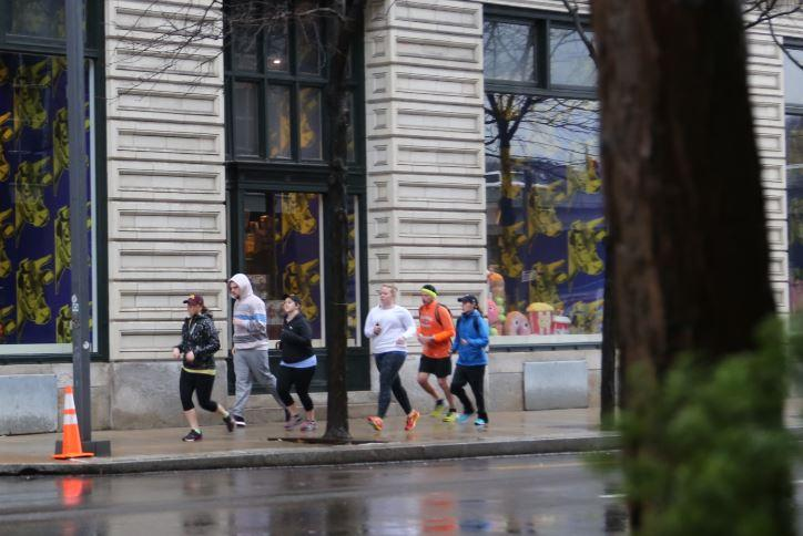 Trista Yerks, left, leads a group of runners through the North Side, in front of the Warhol Museum on Saturday, Feb. 25, 2017.