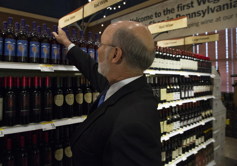 Gov. Tom Wolf buys a bottle of wine at Wegmans in Mechanicsburg, Pa., the first Wegman's wine shop in Pennsylvania as part of the Act 39 liquor reforms.