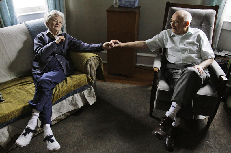 Alzheimer's patient Dorothy Eckert and her husband John Eckert hold hands at their home in Norristown, Pa. The state's Department of Aging is hosting community forums to help caregivers find resources.