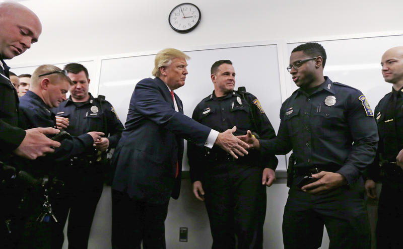 Then-presidential candidate Donald Trump shakes hands with a patrolman, while other officers look at photos of them posing with Trump on Thursday, Feb. 4, 2016, during a campaign stop at police headquarters in Manchester, N.H.