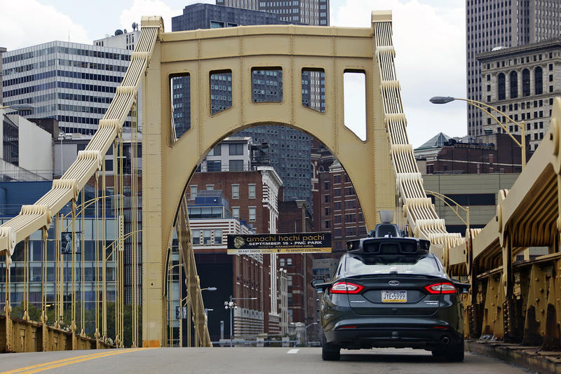 A self-driving Uber car drives across the Ninth Street Bridge in downtown Pittsburgh on Wednesday, Sept. 14, 2016.