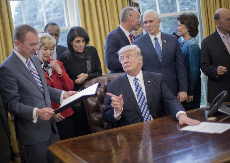 President Donald Trump looks over towards Budget Director Mick Mulvaney, left, after signing an executive order in the Oval Office of the White House in Washington, Monday, March 13, 2017.