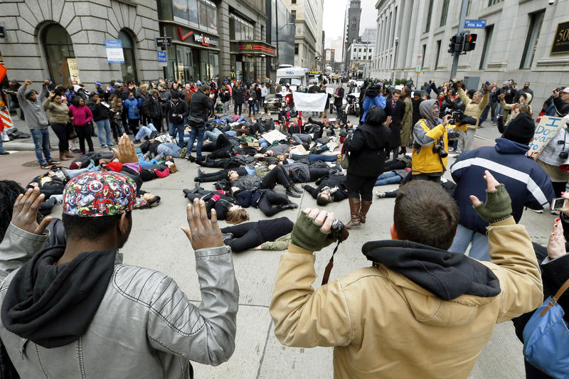 "Demonstrators assume the ""hands up, don't shoot"" position as others protesting the deaths of unarmed black men shot by white police officers lay in the street during a march through Pittsburgh on Thursday, Dec. 4, 2014."