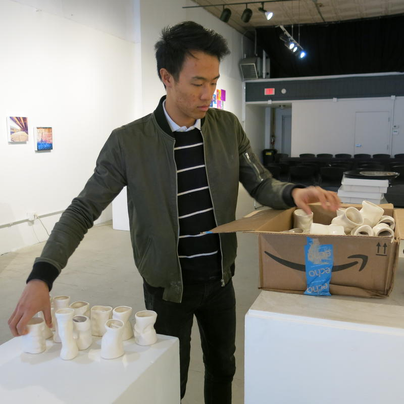 CMU art student Daniel See unpacks the mugs he made using clay impressions of the hands of homeless people.