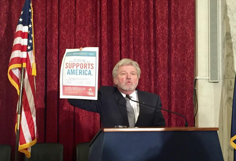Bob Lynch, President and CEO of Americans for the Arts holds up a copy of The Hill newspaper with a full page ad supporting the arts