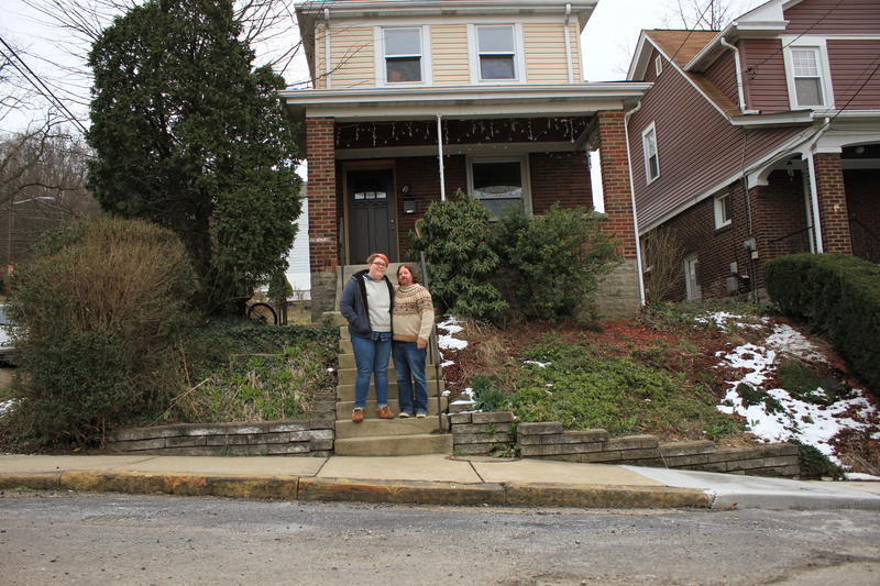 Sabrina Spiher Robinson and her husband Ted Robinson stand on the steps of their home in Upper Lawrenceville. Their street was part of a pilot project from PWSA to coordinate lead service lines replacement with homeowners.