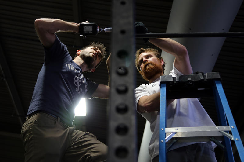 Co-owner Paul Guarino, 32, and route setter Brian Pascuzzi, 30, place the final bolts on a secondhand weight lifting rack in the northeast corner of Ascend's second-floor gym on Sunday, March 5, 2017.
