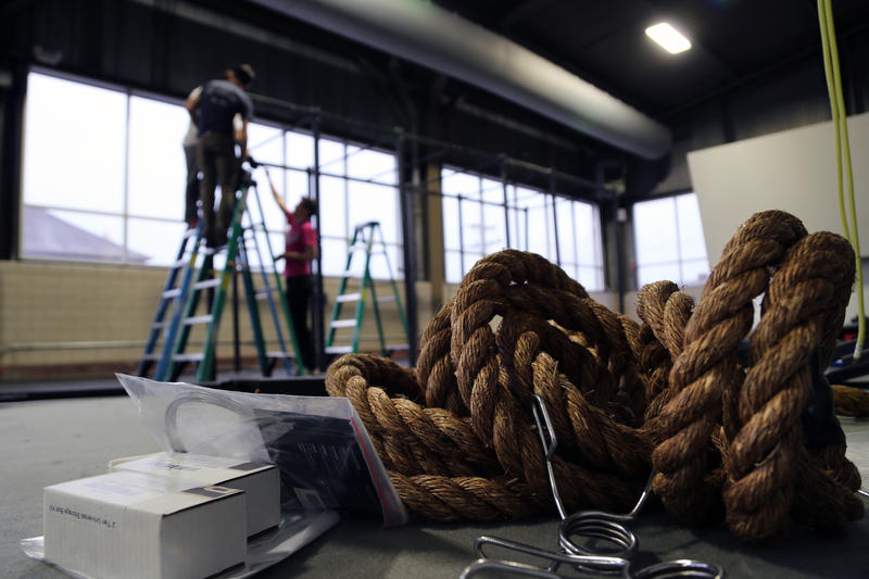 Ropes, gym flooring and tools lay a few feet from Ascend co-owner Paul Guarino, general manager Todd McCormick and new employee Sara Middleton as they put the finishing touches on a weight lifting rack on the far side of the gym's top rope wall.