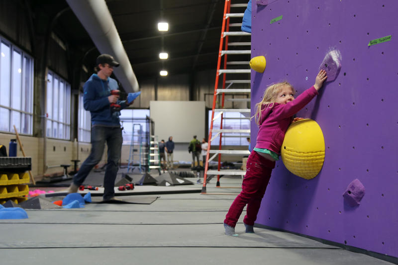 Payton Gilmore, 3, stretches for a purple climbing hold near her father, Aaron, who is the head route setter and co-owner of Ascend.