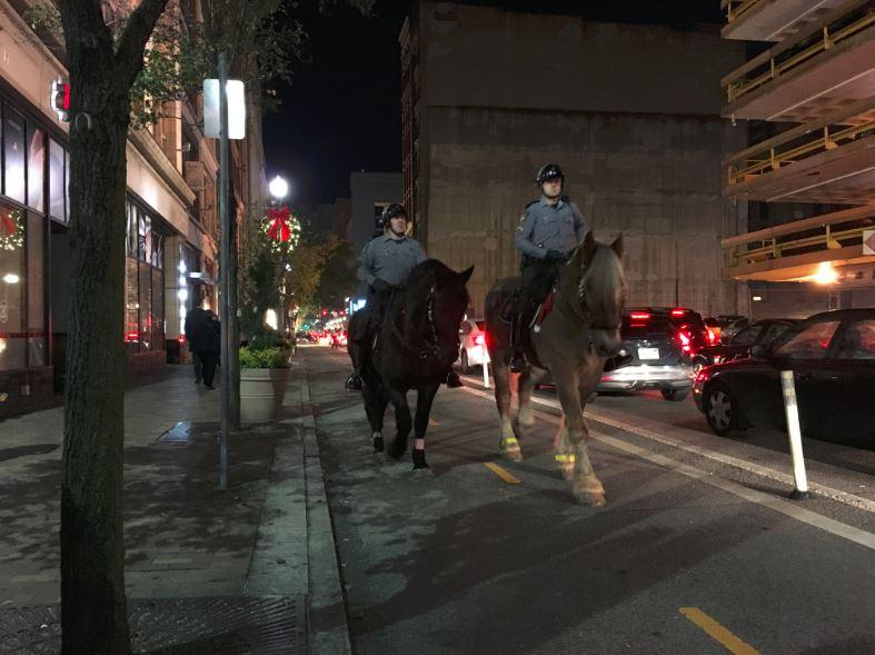 Two Allegheny County police officers ride on horseback through Downtown Pittsburgh on Nov. 18, 2016.