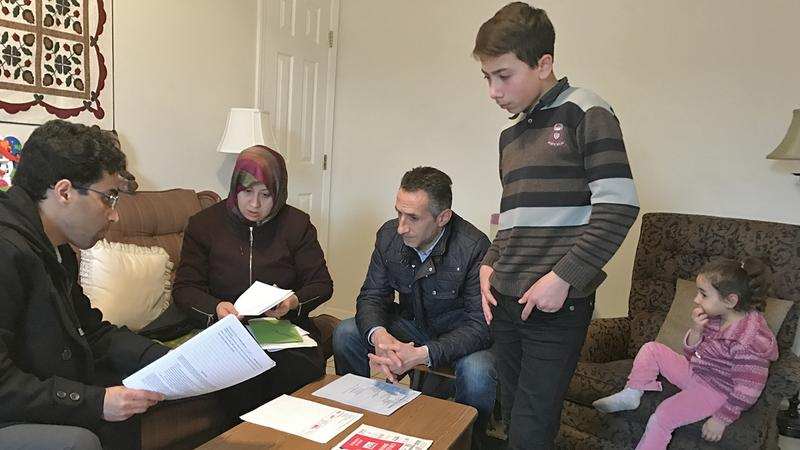 Amer Alfayadh, caseworker for Church World Service's Lancaster office, reviews paperwork with Marwa Hilani, her husband Imad Ghajar and children Mohamad, 14, and Lamar, 4.