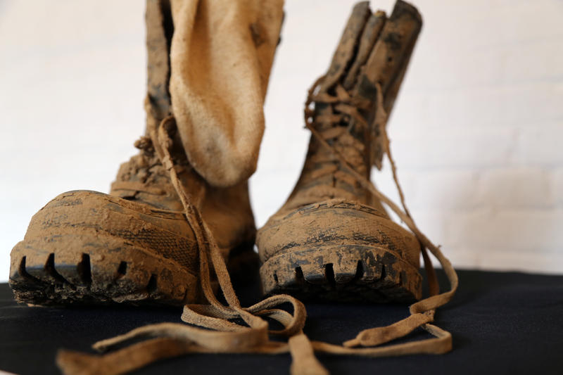 Mud-covered boots from artist Kim Jones' 1990 Mud Man performance, recreating a trek through rice fields in Vietnam.