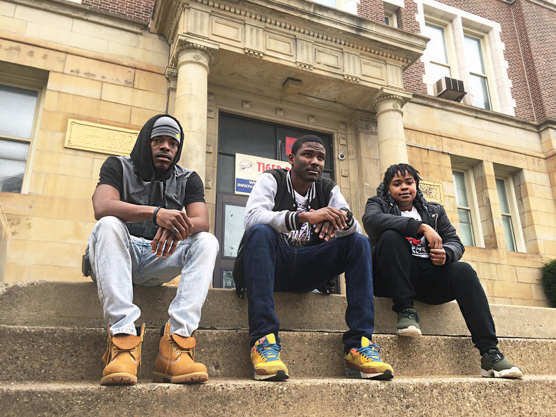 Josh Horton, left, Tehilah Spencer, center, and Sarah Jackson, right, sit outside of the now-closed Wilkinsburg High School.