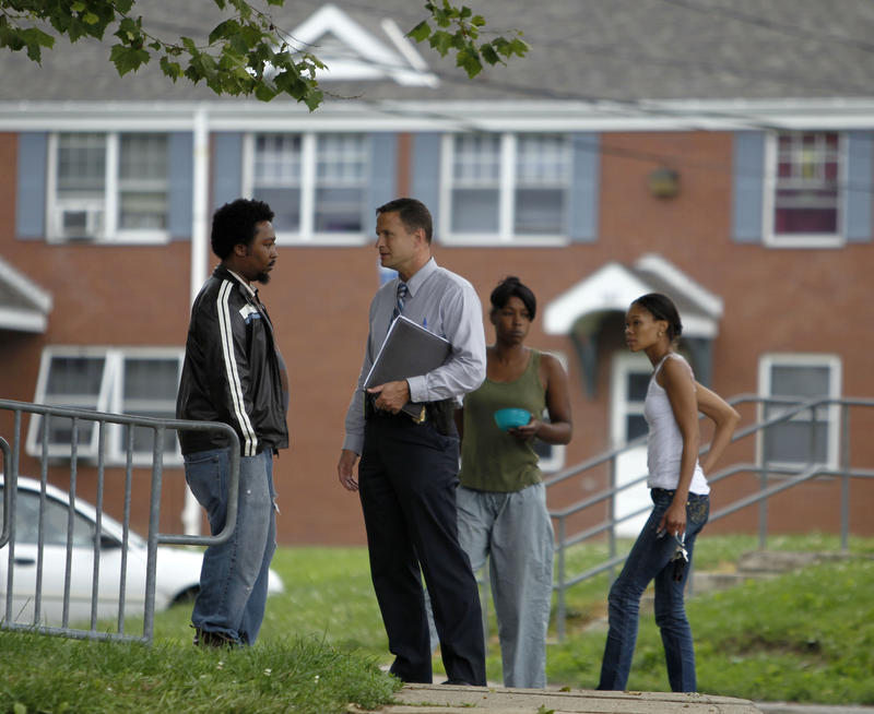 Residents talk with an Allegheny County police detective outside a Crawford Village home where a triple fatal shooting occurred Tuesday, June 15, 2010, in McKeesport.