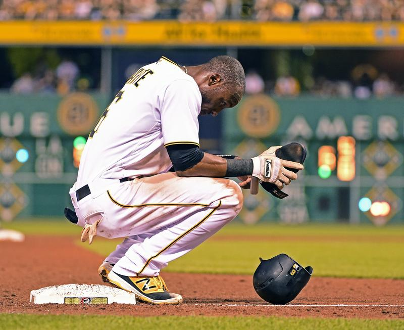 Pittsburgh Pirates' Starling Marte rests at third base during a baseball game against the Miami Marlins in Pittsburgh, Friday, Aug. 19, 2016.