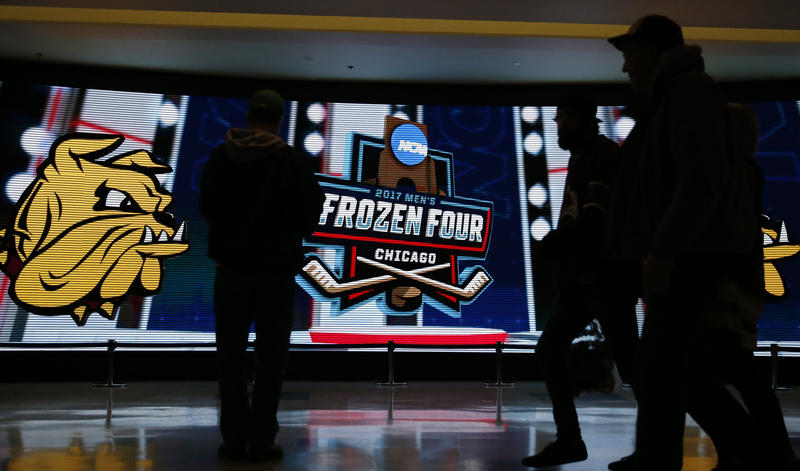 Fans take photos in front of a big screen during the first period of the NCAA Frozen Four men's college hockey semifinal game between Minnesota-Duluth and Harvard on Thursday, April 6, 2017, in Chicago. Minnesota won 2-1.