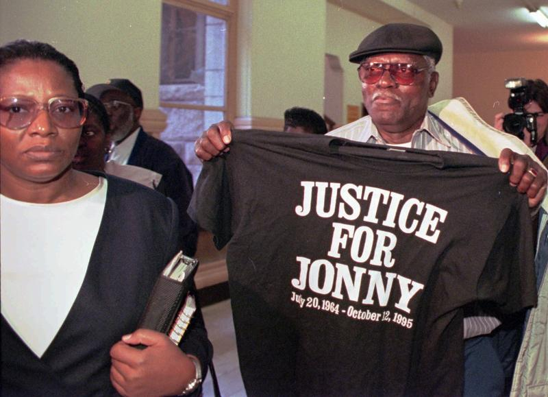 "Jonny Gammage Sr., father of Jonny Gammage, leaves Allegheny Courthouse for lunch holding a ""Justice For Jonny"" t-shirt, with Jonny's aunt Blonirene Seals, left, during the first day of trial Oct. 15, 1996, against two white suburban police officers."