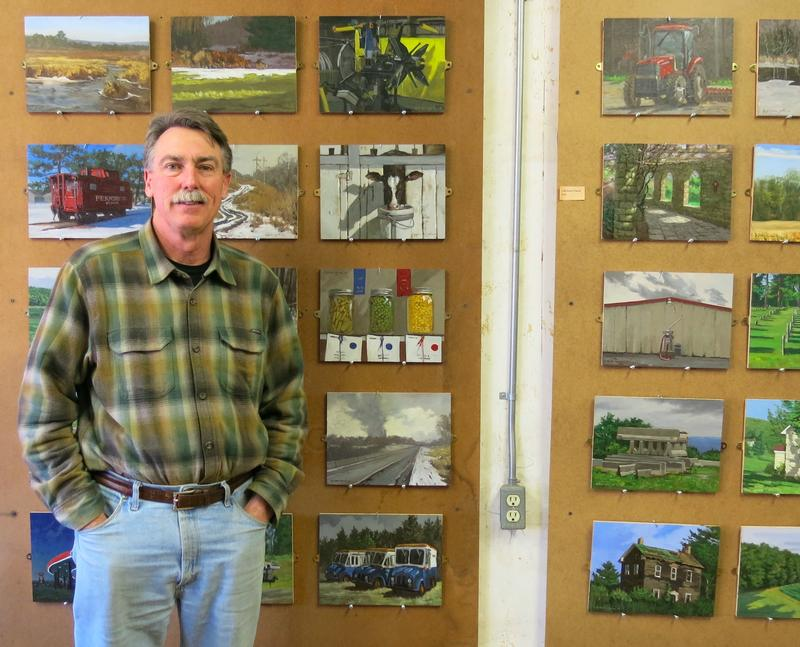 Pittsburgh landscape artists Ron Donoughe, beside some of the paintings he's done of Cambria County, where he grew up.