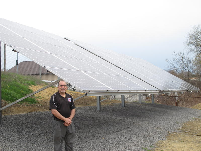 Monaca Borough Manager Mario Leone stands next to half of the solar panels installed at the borough's water reservoir.  The remainder of the panels are on top of a public works garage.