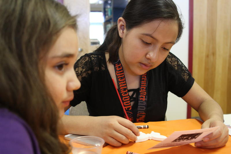 Shayla Esquivel, 12, reads a biographical card of a child who died in the Holocaust.