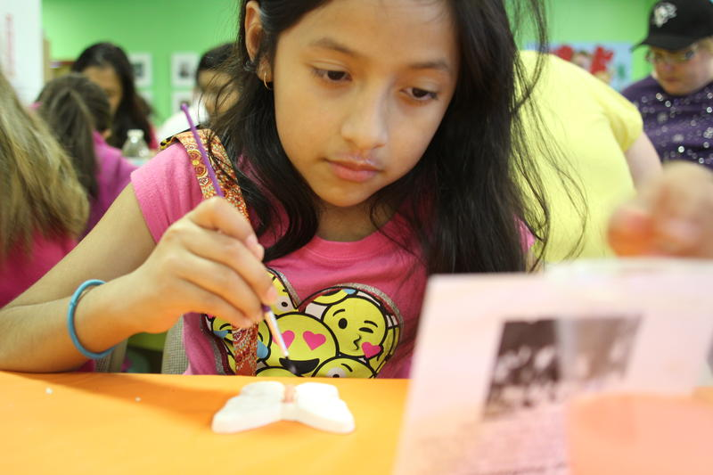 Luz Esquivel, 9, reads a biographical card of a child who died during the Holocaust.