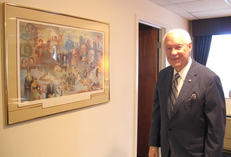 Jim Roddey, who helped create the current form of government in Allegheny County and served as it's first Executive, stands in his office near a picture depicting famous Pittsburghers.