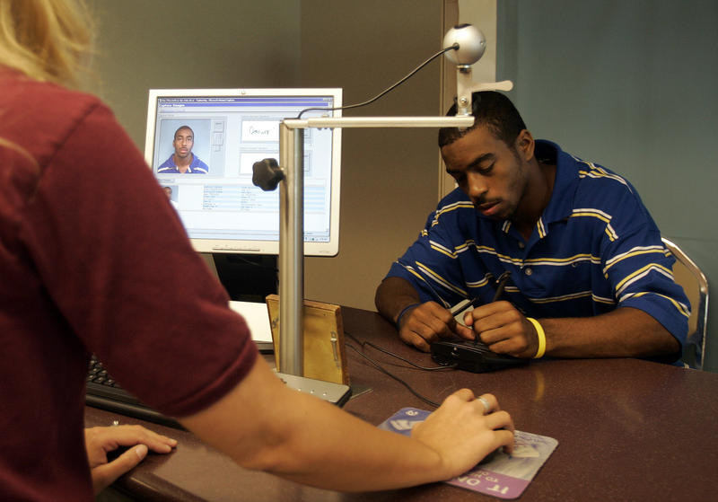 Darius Reeves, 16, right, of Columbus signs his signature as Francheska Welsh, customer service specialist, processes his drivers license at the Ohio Department of Motor Vehicles in this Aug. 23, 2006 file photo. '