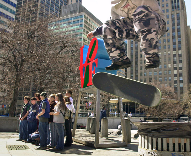 Mike Cole, of Jenkintown, right, performs a kick-flip over a trash can with his skateboard as tourists pose for photos in front of artist Robert Indiana's sculpture in JFK Plaza, also known as Philadelphia's Love Park, on April 1, 2002.