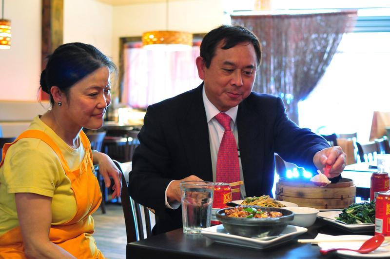 Dr. Freddie Fu explains to Jenny Tao that he has a unique way of eating soup dumplings by dunking the whole thing in the sauce to cool it off.