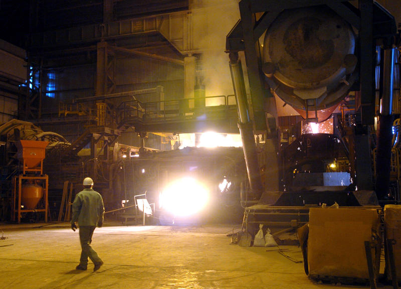 A steelworker walks past an electric arc furnace at Wheeling Pittsburgh Steel Corp's facility in Mingo Junction, OH on Wednesday, June 1, 2005.