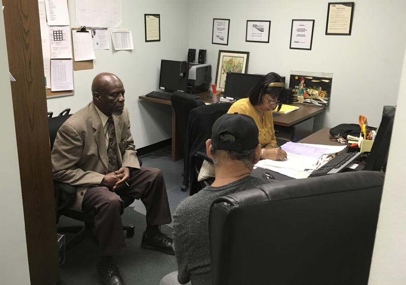 In this May 18, 2017, photo, Nathan Singletary, 67, a social worker for 40 years, listens as Employment Specialist Luz Rivera, 68, interviews program participant Luis Quinones, 66, front right, at the AARP Foundation in Harrisburg, Pa.