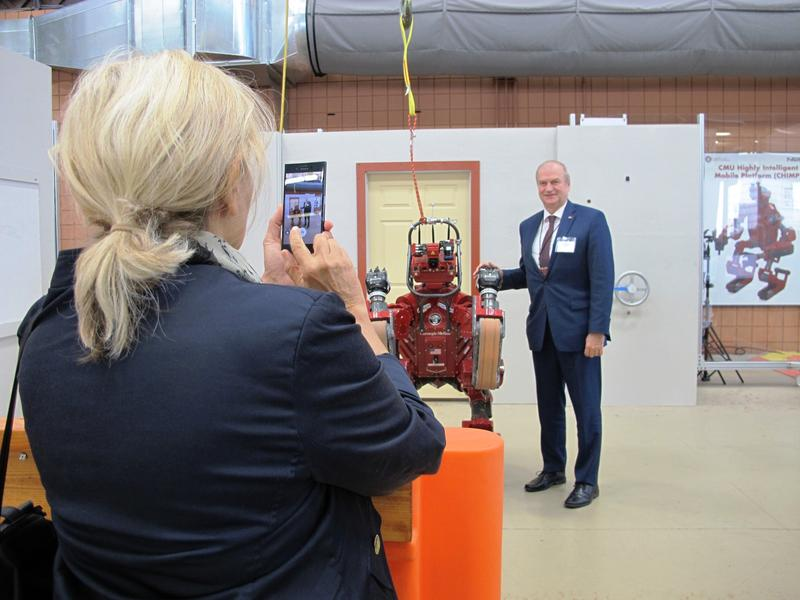 Serbian ambassador Derd Matkovich poses with CMU's CHIMP robot at the National Robotics Engineering Center on Tuesday, May 23, 2017.