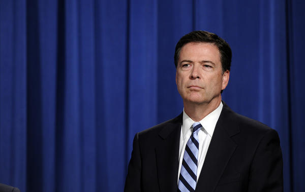 Then-FBI Director James Comey listens during a news conference announcing a deal between the U.S. Government and French bank ENP Paribas at the Justice Department in Washington, Monday, June 30, 2014.