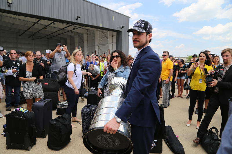 Pittsburgh Penguins team captain Sidney Crosby holds the Stanley Cup as he's greeted by fans upon the team's arrival in Pittsburgh.
