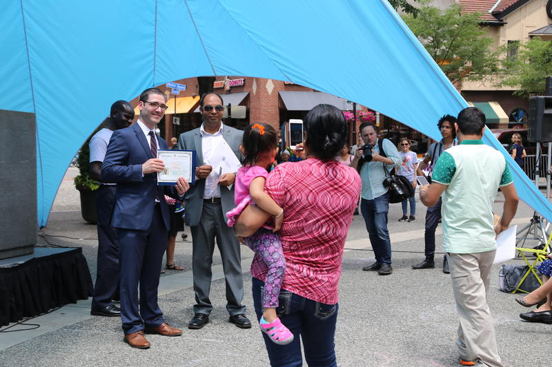 Families watch and take photos as certificates of citizenship are distributed.