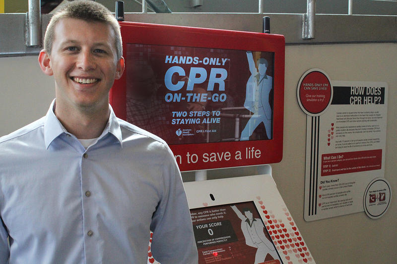 Sean Ferguson poses for a portrait in front of a kiosk that teaches CPR. A student at his school had learned CPR from a similar kiosk and helped save Ferguson's life two years ago.