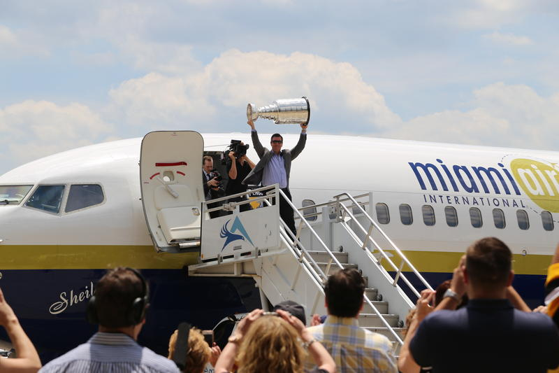 Penguins head coach Mike Sullivan arrives at Atlantic Aviation at Pittsburgh International Airport hoisting the Stanley Cup.