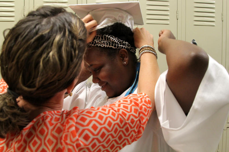 Melissa Love, left, a special education teacher at Urban Pathways 6-12 helps Denisha Foster, 19, put on her cap before seniors walked through elementary school classrooms telling students what they were doing after graduation.