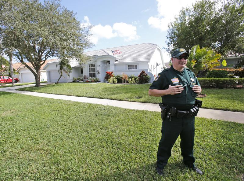 A Palm Beach County Sheriff's deputy keeps watch over the home of a police officer in Lake Worth, Fla., in October 2015. The officer, Nouman Raja, set off protests when he fatally shot 31-year-old Corey Jones while investigating local burglaries.