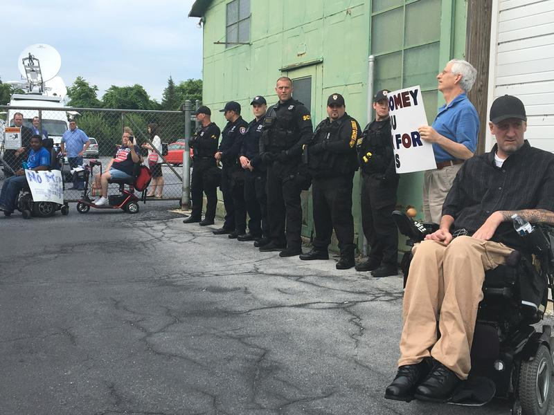 Protesters with the group ADAPT, which advocates for people with disabilities, rally outside of a TV studio in Harrisburg where Republican Sen. Pat Toomey held a live town hall.