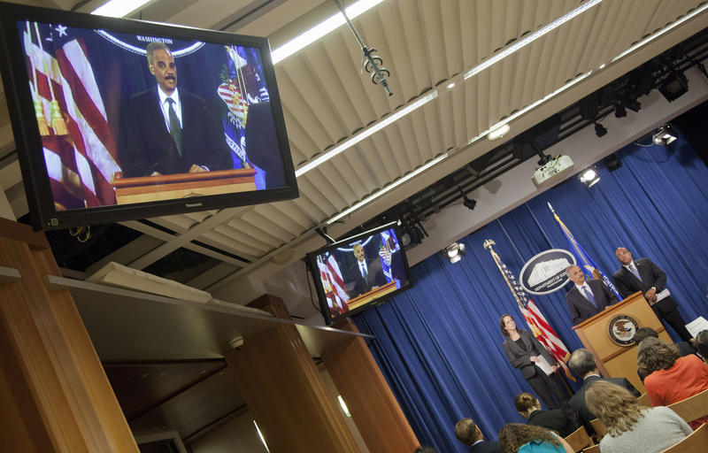 Attorney General Eric Holder is seen on an in-house television monitor as he speaks during a news conference at the Justice Department in Washington, Thursday, Sept. 4, 2014. COPS director Ronald Davis (right) looks on.