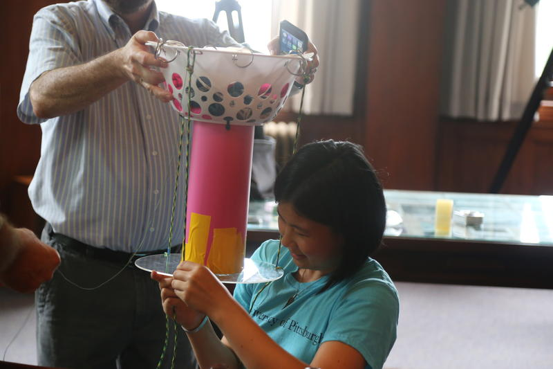 Rising Pitt sophomore Grace Chu adds final touches to one of the balloon's payload tubes using colored duct tape on Friday, July 14, 2017. The payload contains cameras, light sensors, internet modems and computers.