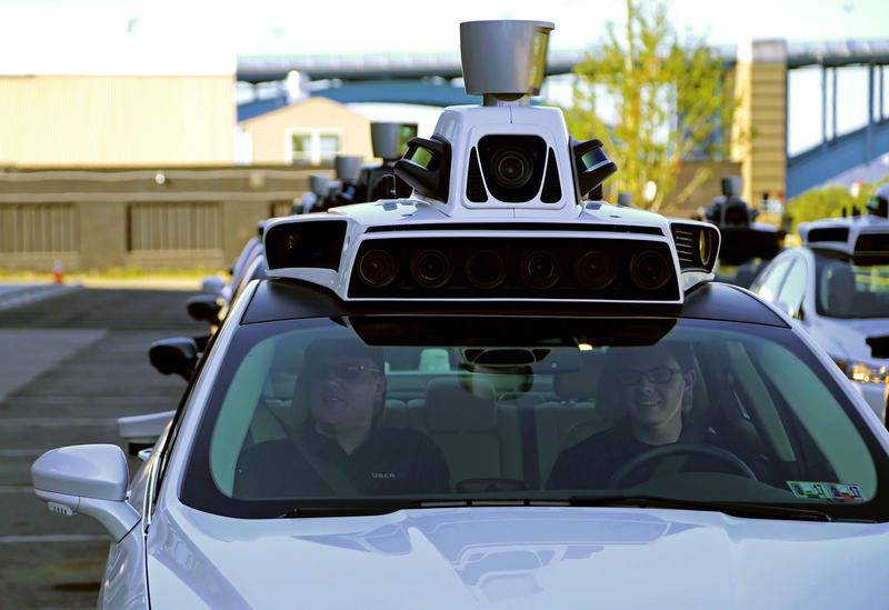 Uber technicians sit an a self-driving Ford Fusion outside the Advanced Technologies Center in Pittsburgh on September 13, 2016.