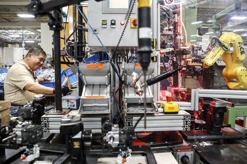 An assembly line laborer works across from a collaborative robot, right, at the Stihl Inc. manufacturing facility in Virginia Beach, Va., on Thursday, May 25, 2017. At the plant, human workers are interpersed with computers and robotics.