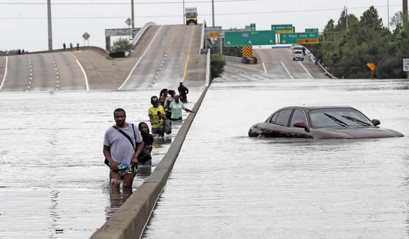 Evacuees wade down a flooded section of Interstate 610 as floodwaters from Tropical Storm Harvey rise Sunday, Aug. 27, 2017. The remnants of Hurricane Harvey sent devestating floods pouring into Houston.
