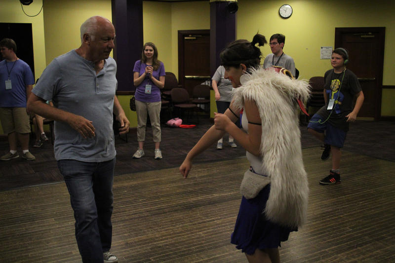 Camp director Joey Travolta dances with a camper during a daily dance party.