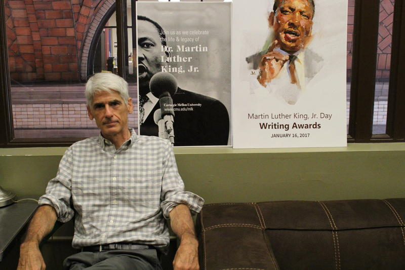 Jim Daniels, the Thomas Stockham Baker University Professor of English and founder and director of the Martin Luther King Jr. Day Writing Awards, poses for a portrait near the posters made for the awards.